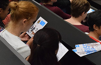 Students in a lecture theatre with Careers branded leaflets