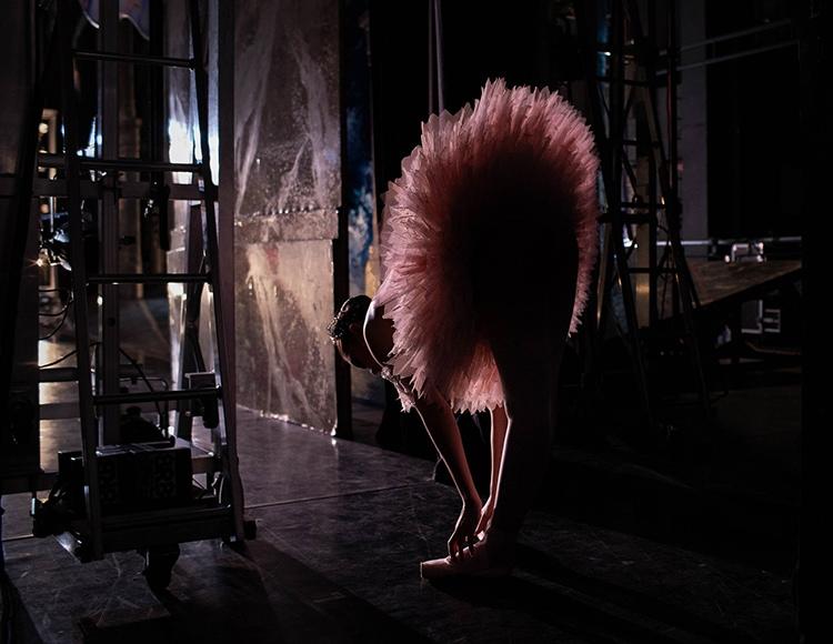 Birmingham Royal Ballet image of a ballerina in a tutu, bending over to tie her shoe