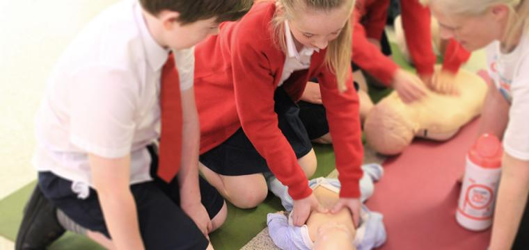 School children practising resuscitation techniques on a baby doll