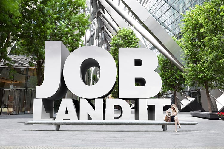 "Campaign image for University of York careers and placements. Professional looking young woman in a modern office building, with huge 3D words ""Job. Land It'"" behind her."