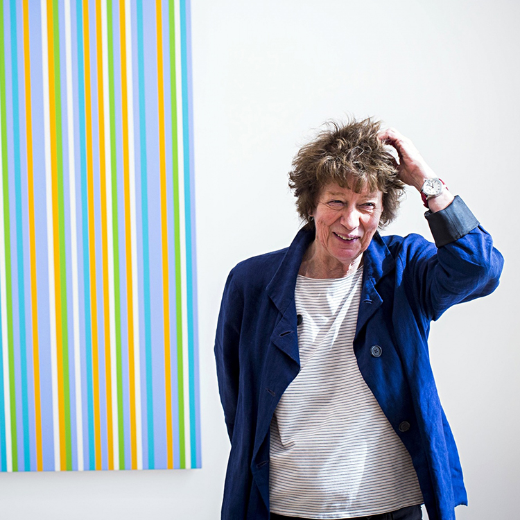 Artist Bridget Riley in front of one of her pieces