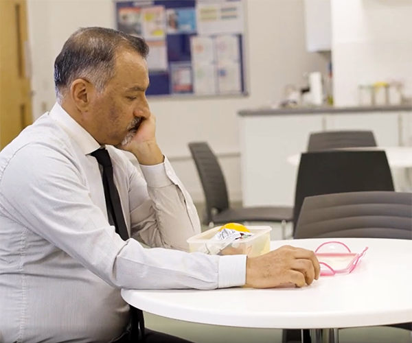 Still from the Finding it Tough videos of a man looking fed up in an office kitchen